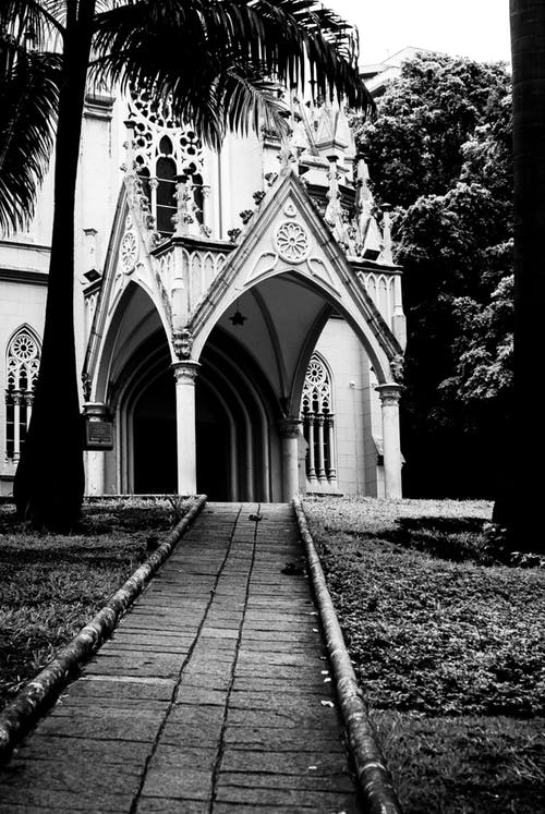 Black and white of narrow walkway leading to Catholic cathedral with ornamental elements and arched passage