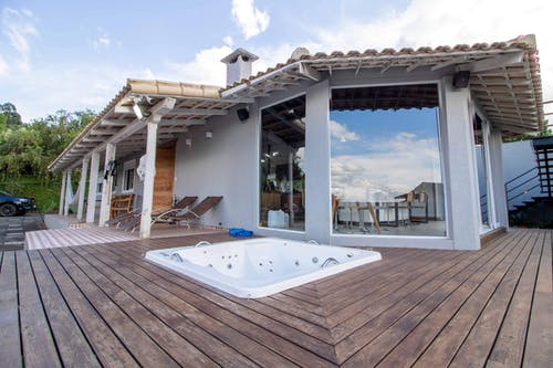 Low angle of luxury villa with glass walls and loungers placed on board floor near bathtub on terrace