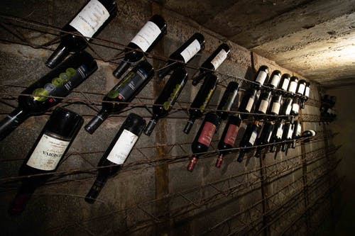 Rows of glass bottles filled with various wine in cellar with gray concrete walls