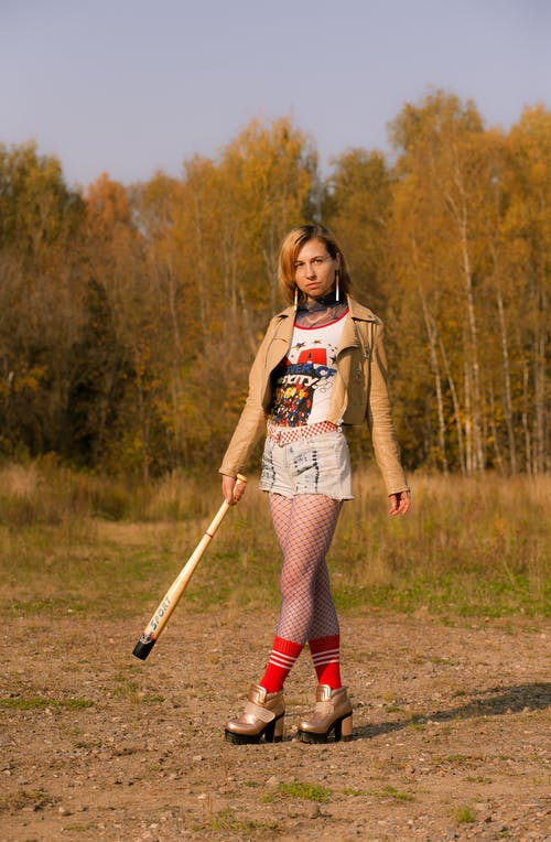 Young informal woman with baseball bat standing in nature