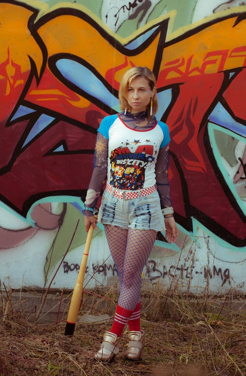 Young informal woman with baseball bat standing against vandalized wall