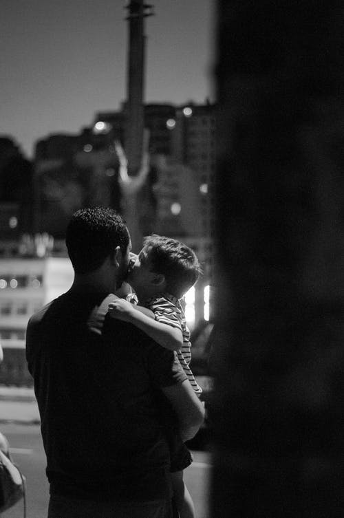 Son kissing father on cheek in evening street of city