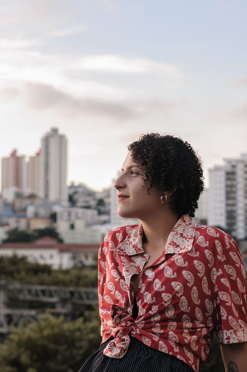 Positive woman with short curly hair admiring city