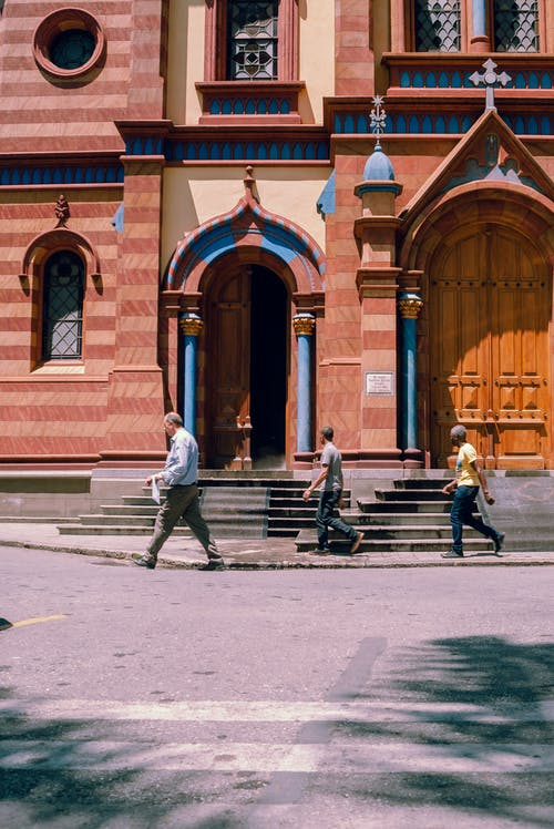 Side view of people walking on sidewalk on street near building with ornamental walls in daytime