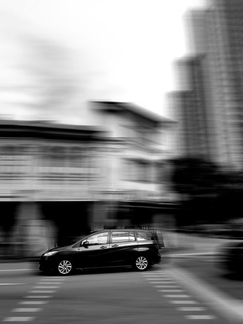 Grayscale Photo of Black Sedan on Road