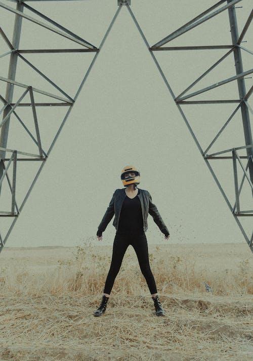 Anonymous female in stylish black wear and boots standing in biker helmet in field near metal construction