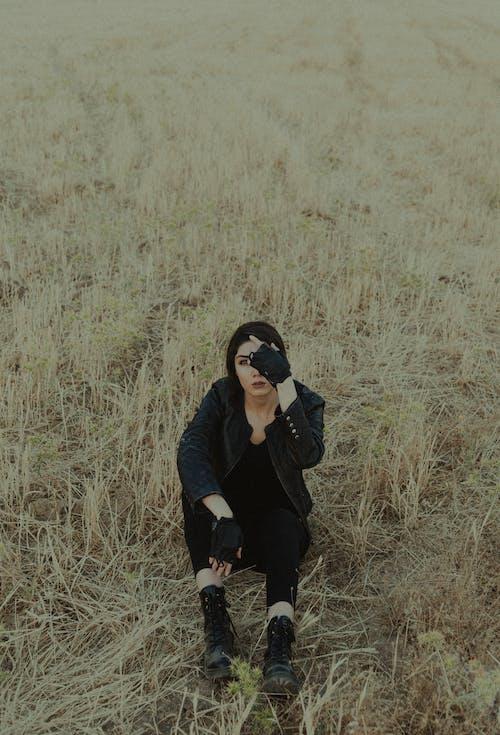 Stylish woman in black apparel resting on grass in field