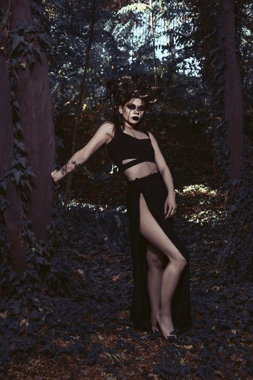 Full body of barefoot lady in black apparel and dark scary makeup standing near tree in forest
