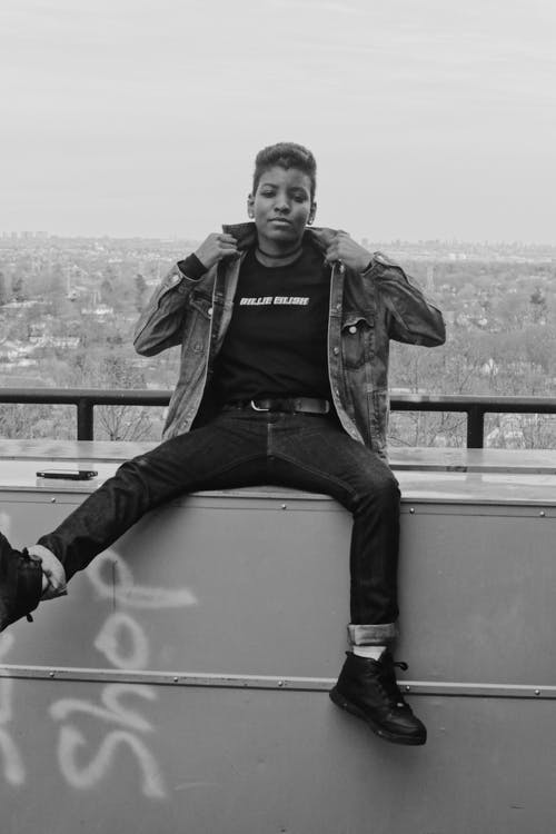 Black and white of cool African American female in denim jacket with short hair looking at camera in town