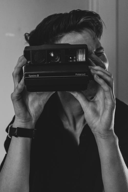 Photographer taking photo on modern instant camera