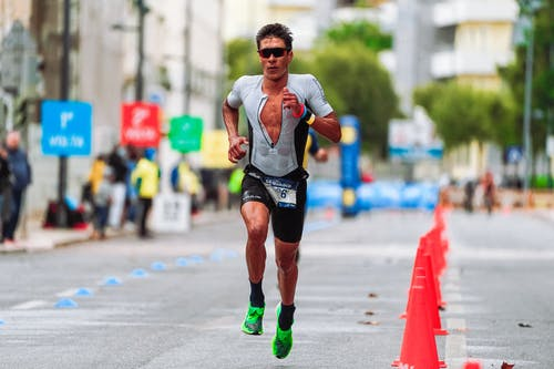 Man in White T-shirt Running on Road