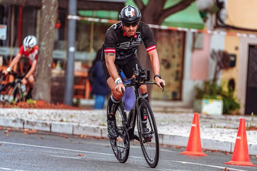 Man in Black Helmet Riding on Black Bicycle on Road