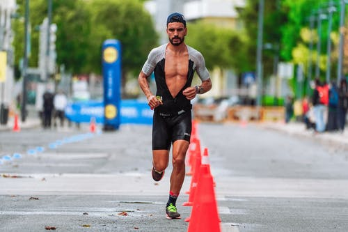Man in Black Top and Black Shorts Running on Road