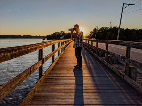 Man and Woman Kissing on Wooden Dock