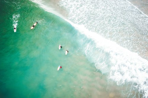 Picturesque drone view of unrecognizable people riding waves on surfboards in powerful turquoise ocean with sandy beach