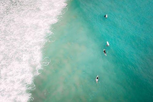 Unrecognizable people on surfboard in wavy sea with foamy waves