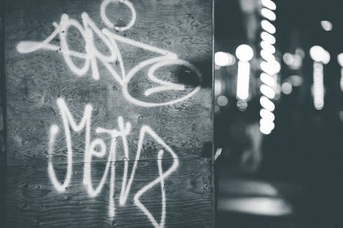 Black and white vandal graffiti on wall against bright shining lamps of street