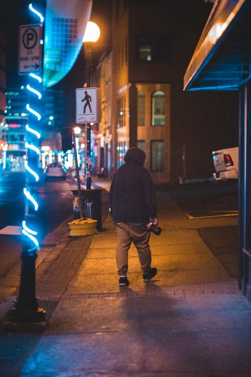 Full body of anonymous male with photo camera strolling on sidewalk with glowing garlands on poles