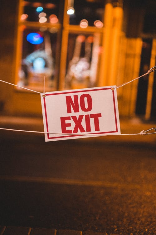 Bright restricting sign saying no exit hanging on road of city at night