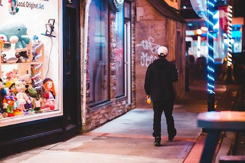Man walking on sidewalk near illuminated showcases