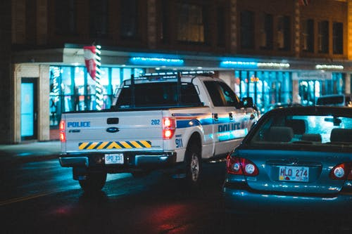 Police pickup with tail light riding on asphalt roadway near car along building with glass showcase in city on evening time