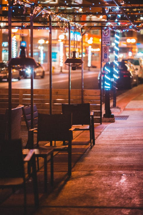 Metal construction with garland located on pavement with chairs and benches near road on illuminated street in city on evening time