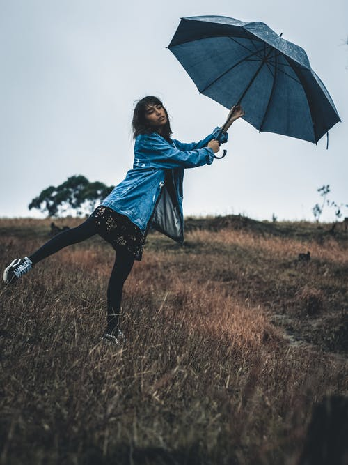 Full length young calm female in casual wear holding umbrella and standing on one leg on grassy meadow on rainy day