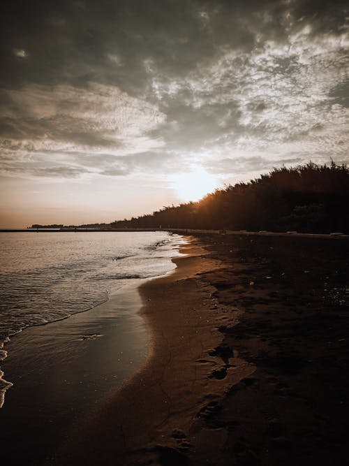 Bright sunlight shining on sunset sky over waving sea washing sandy beach in cloudy day