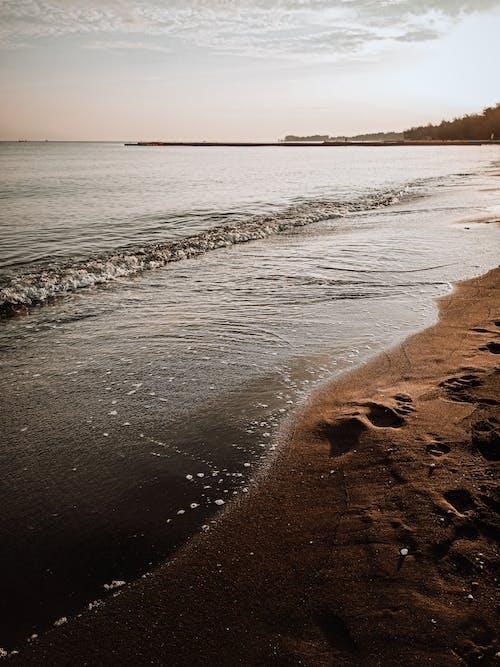 Sandy beach washed by waving sea