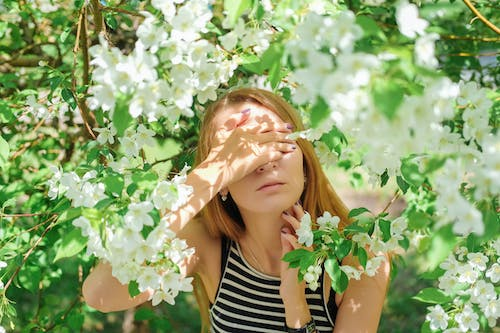 Woman covering eyes with hand and standing in blooming garden