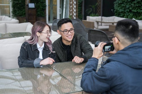 Man taking pictures of happy young Asian friends while sitting together at table in outdoor restaurant