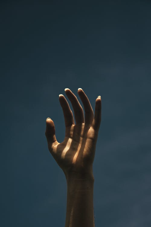 Persons Left Hand on Blue Sky