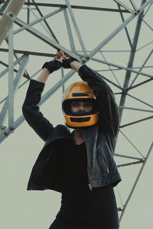 Female biker in helmet under metallic tower