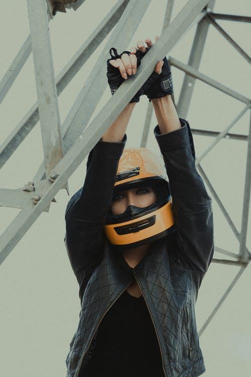 From below of young attentive female in biker helmet standing with raised arms while touching metallic construction and looking at camera