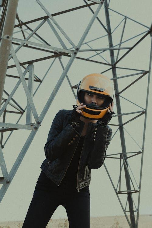 Trendy female biker in helmet under metal tower