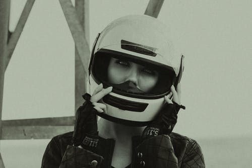 Black and white of attentive lady in stylish outfit and helmet looking at camera