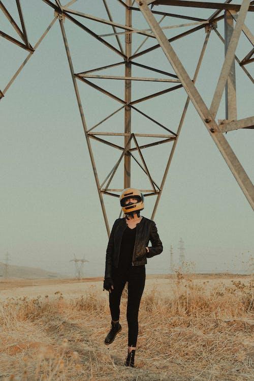 Woman in helmet and black apparel in field