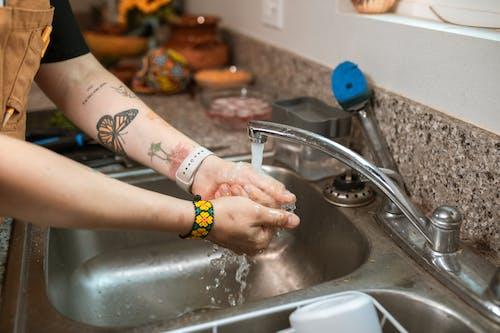 Person Im Gelben Und Schwarzen Armband, Das Hände Auf Waschbecken Wäscht