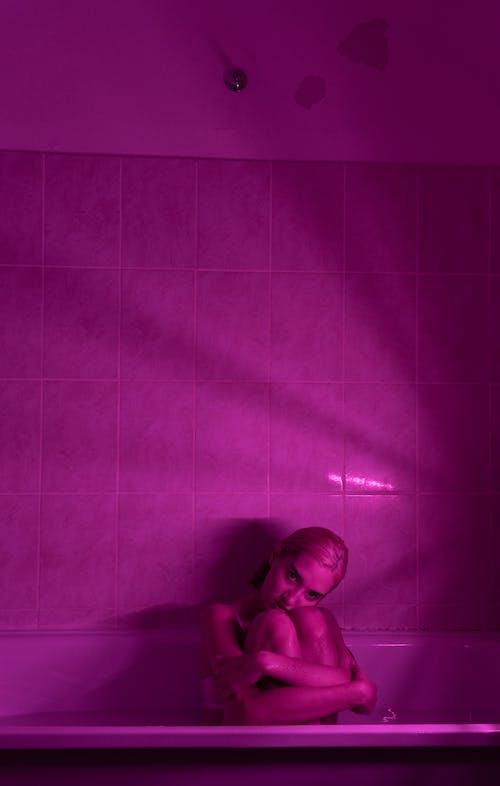 Sensual woman in bath with neon light