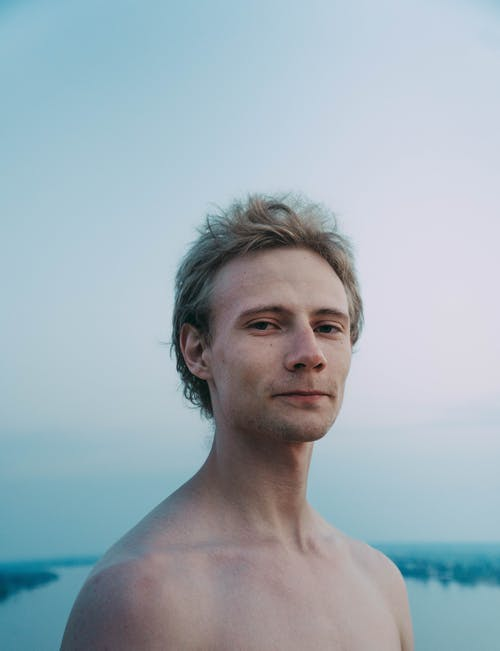 Young friendly male with naked torso and uncombed hair looking at camera against river in daytime