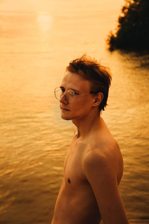 Shirtless man contemplating nature against river in twilight