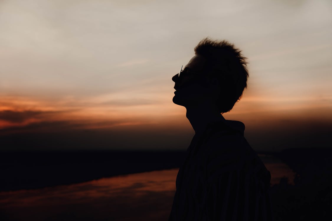 Side view of lonely male silhouette in eyeglasses breathing and admiring cloudy sky at night