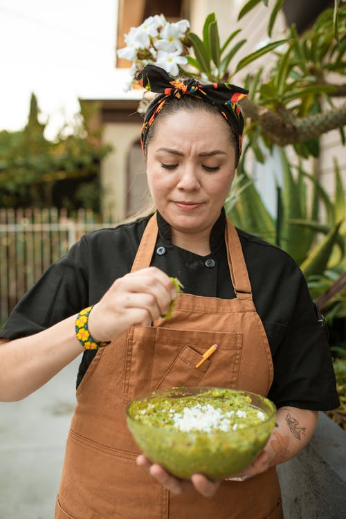 A Female Chef Squeezing a Lime into a Bowl of Guacamole