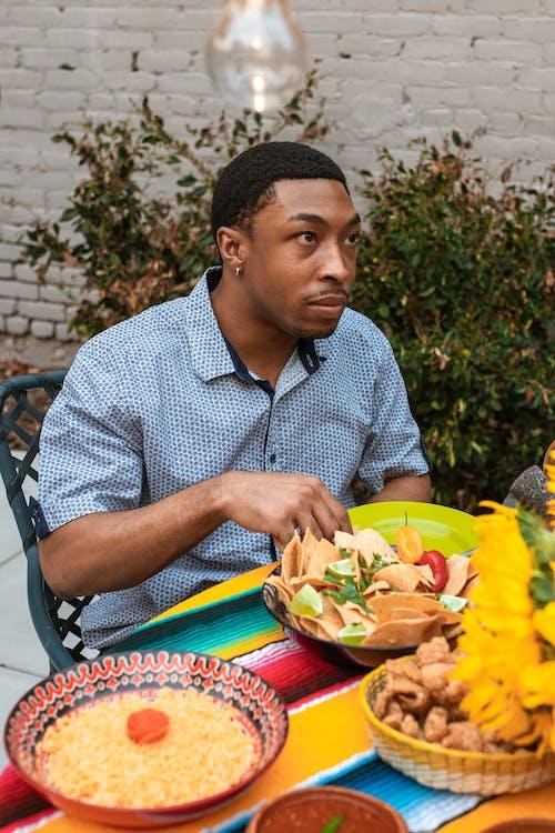 검은 강철 의자에 앉아 파란색과 흰색 체크 무늬 버튼 업 셔츠 남자