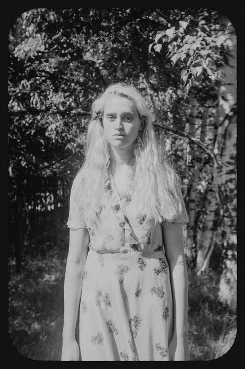 Black and white of young tender female in ornamental outfit looking at camera against birches in sunlight