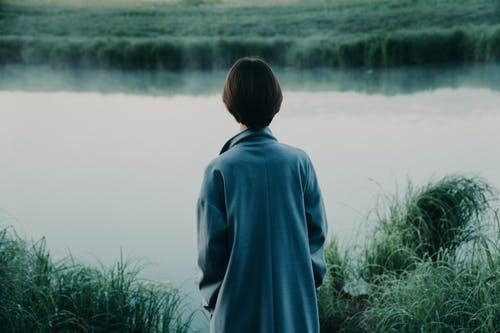Back view of anonymous person in coat admiring river reflecting lush grass in summer in daylight