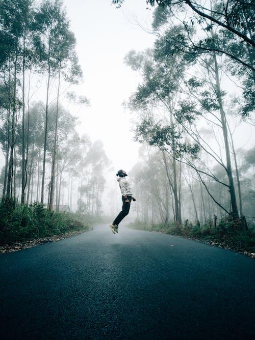 Energetic man jumping on asphalt road