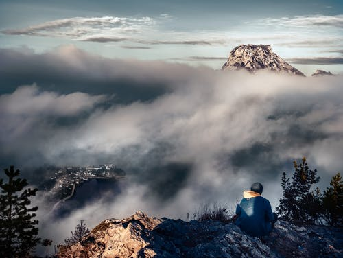Person in Blue Shirt Sitting on Rock Formation Near Clouds