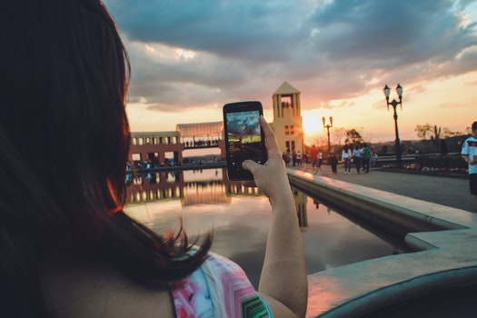 Woman Holding Smartphone Capturing Sunset