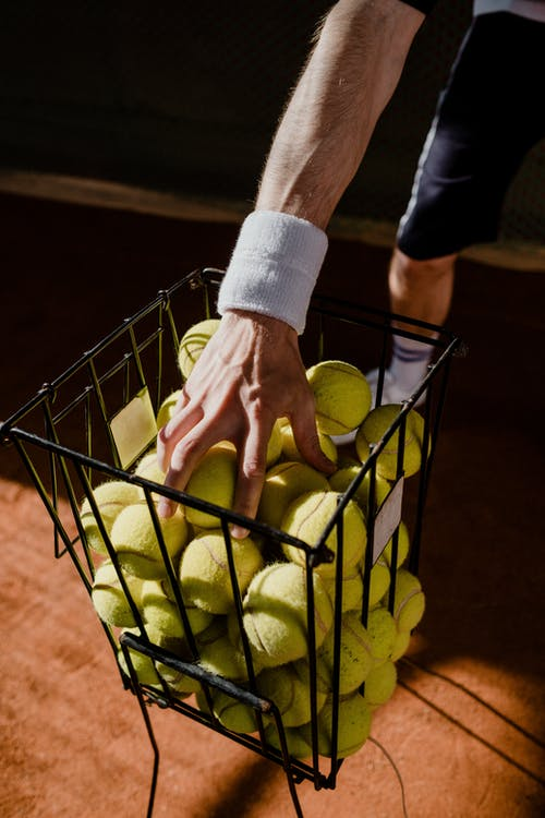Person Holding Green Tennis Balls in Black Metal Basket